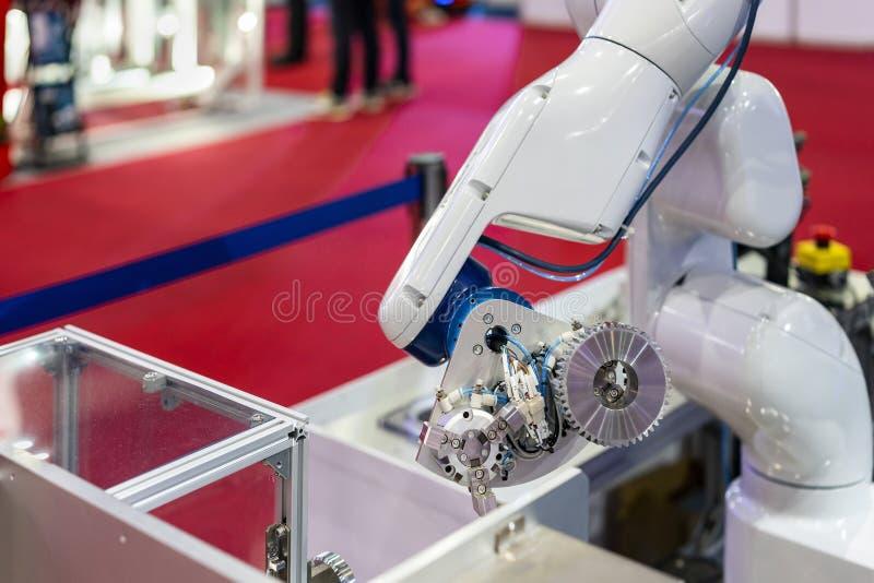 高技术和精确度与自动钳位的机器人抓住齿轮或产品工作片断的夹子或牛颈肉在制造业中 库存照片