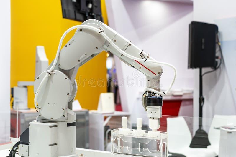 高技术&精确度与自动钳位的机器人抓住工业汽车零件的夹子或牛颈肉这样金属或塑料 库存照片