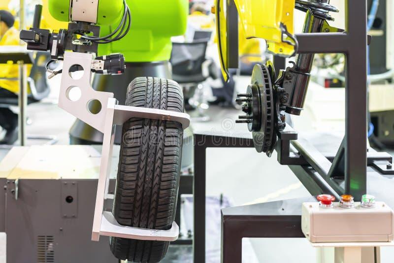 高技术&精确度与自动钳位的机器人抓住轮子和轮胎的夹子或牛颈肉去除或汇编与汽车 库存照片