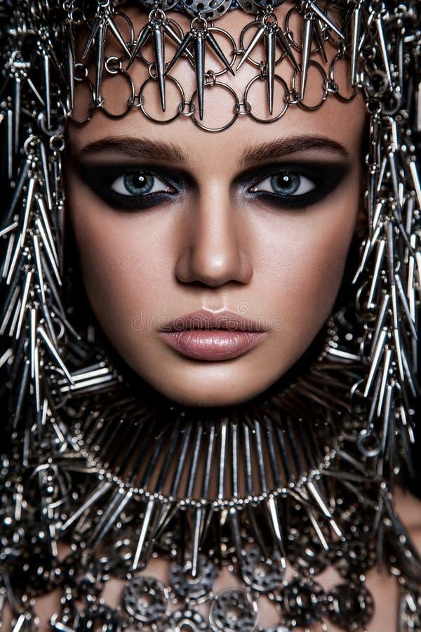 高档时尚与金属headwear的秀丽模型和在黑背景的黑暗的构成和蓝眼睛 免版税图库摄影