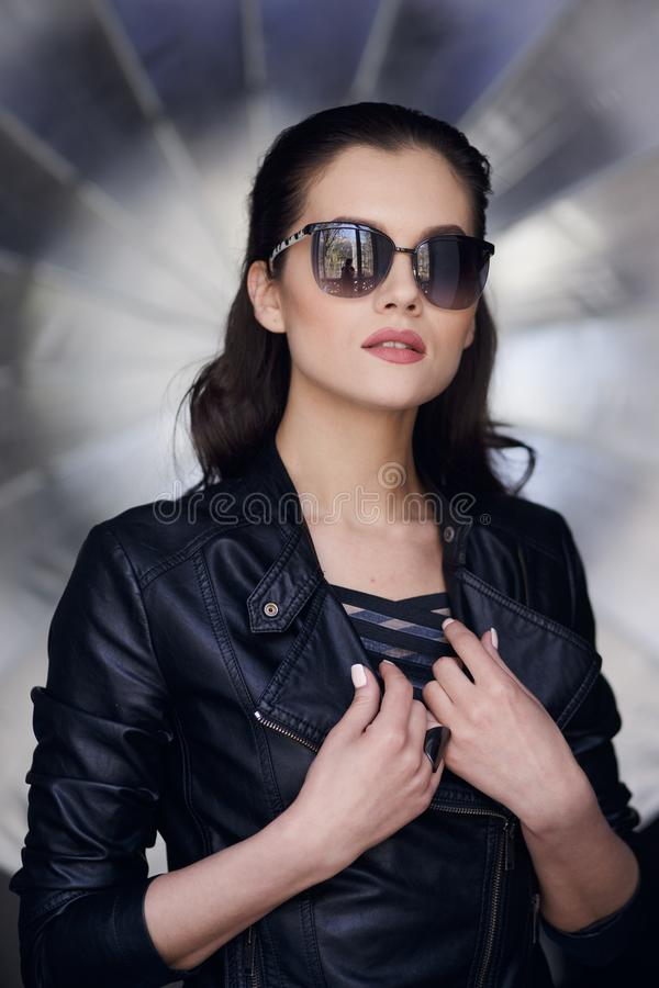 高档时尚神色,性感的深色的女孩,佩带在一副黑皮夹克和时髦的太阳镜,有完善的构成的 库存照片