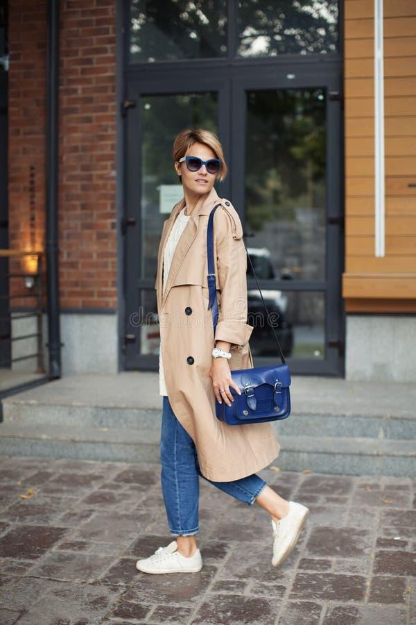 高档时尚衣物 佩带时兴的春天或秋天的美女给米黄军用防水短大衣,蓝色袋子,牛仔裤穿衣, 库存图片