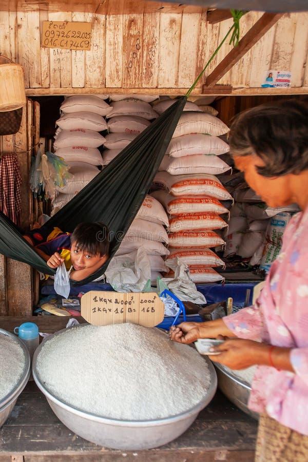 高棉年轻男孩在等待的吊床在卖长粒米在地方市场上 东钳子市场,戈公岛,柬埔寨 免版税库存图片