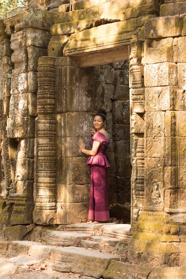 高棉礼服的柬埔寨女孩在古老大厦门道入口  免版税库存照片