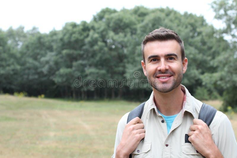 高涨男性人纵向微笑的走的年轻人的森林愉快的远足者 走在森林里的男性远足者 免版税库存图片