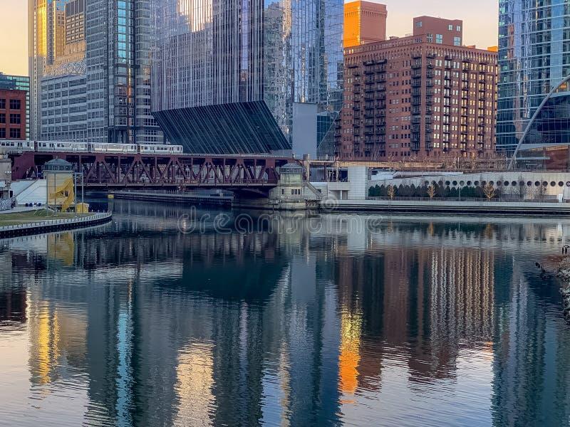 高的火车仍然横渡有围拢的都市风景的表面反射的芝加哥河 免版税库存照片