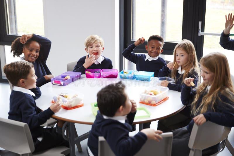 高的观点的一起坐在圆桌上的小学孩子吃他们的被包装的午餐 库存照片