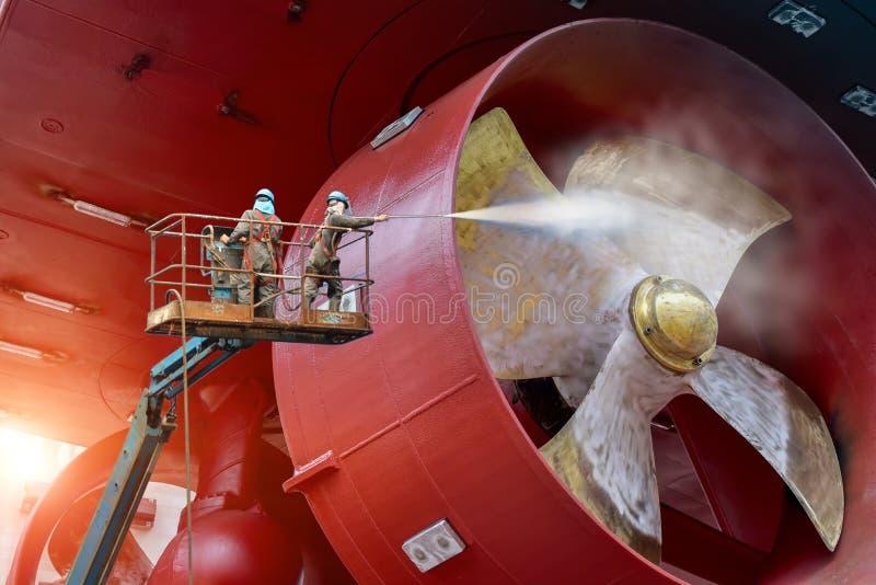高穿戴安全带的工作者在喷气机水高压的洗涤的推进器船下 库存照片