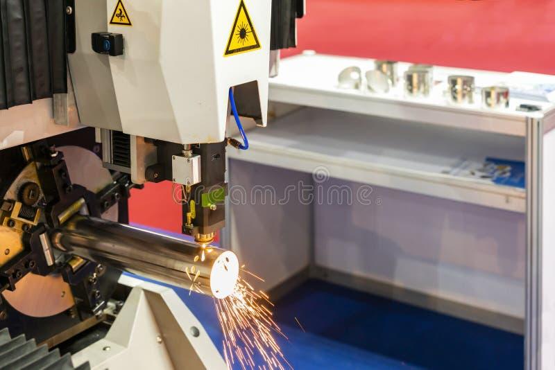 高精度cnc等离子激光切割机接近的喷管在期间刻记或穿孔制件管子并且发火花与 免版税库存照片
