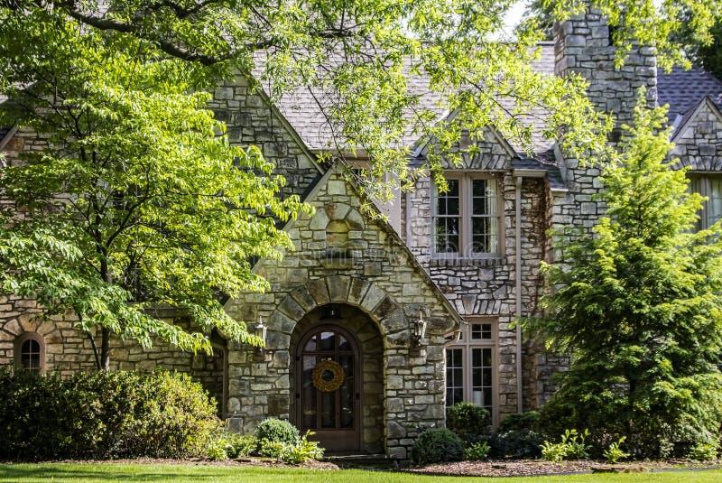 高级多有山墙的岩石房子入口有被成拱形的门廊的和与花圈的前门和茂盛植物和环境美化 免版税库存照片