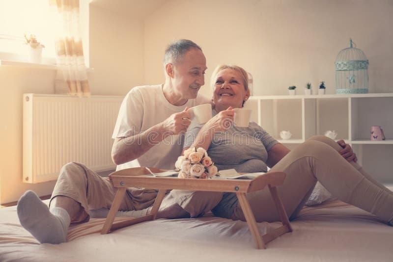 高级夫妇在河床上 资深人民饮用的咖啡在床上 免版税库存照片