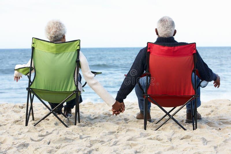 高级夫妇坐海滩在Deckchairs 免版税图库摄影