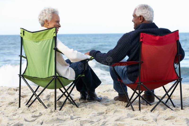 高级夫妇坐海滩在Deckchairs 库存照片