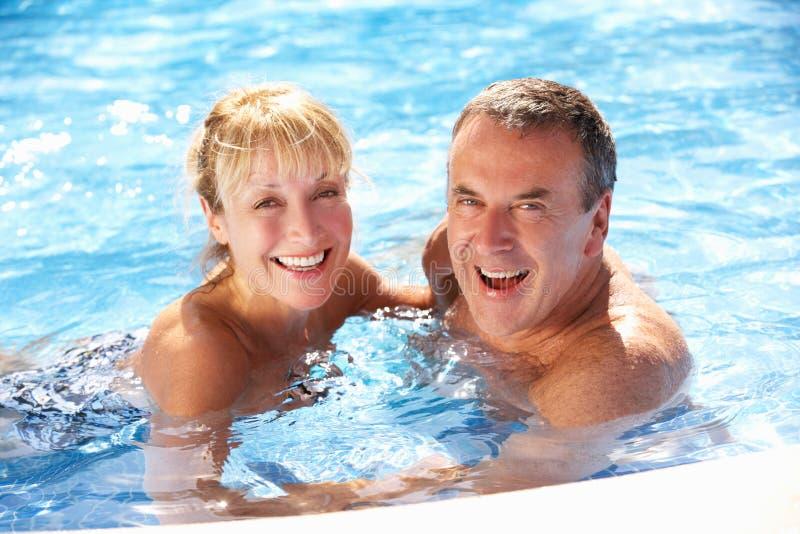高级夫妇获得乐趣在游泳池 库存图片