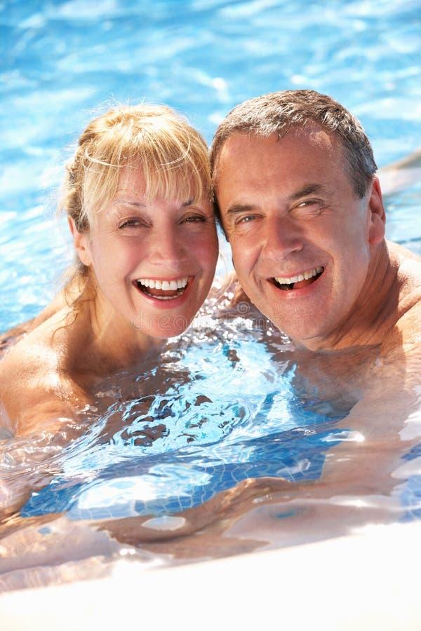 高级夫妇获得乐趣在游泳池 免版税库存图片