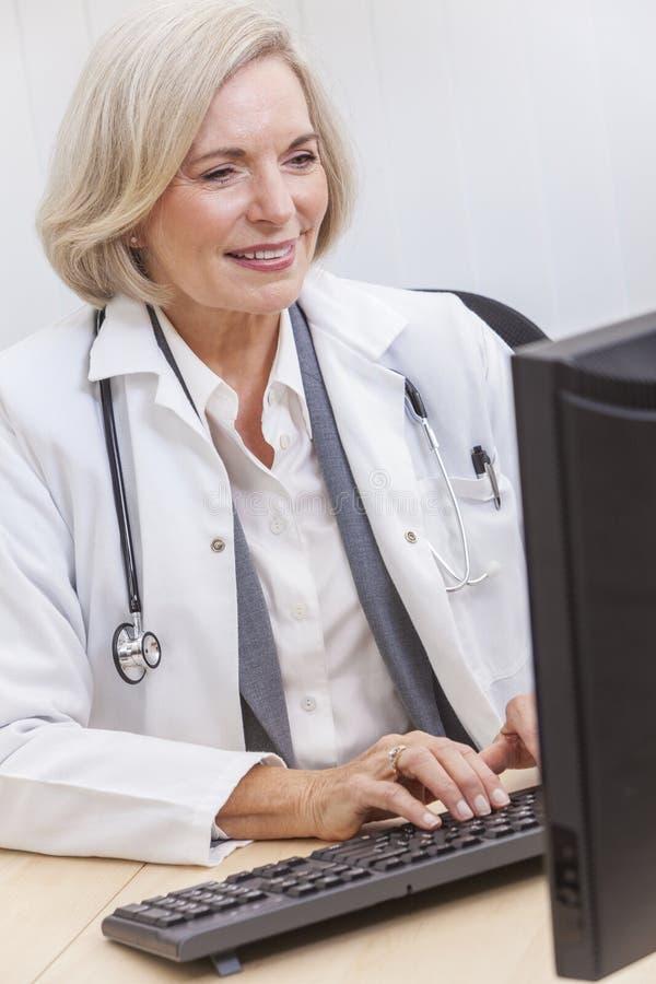 高级女性医生在服务台&计算机的With Stethoscope 库存图片