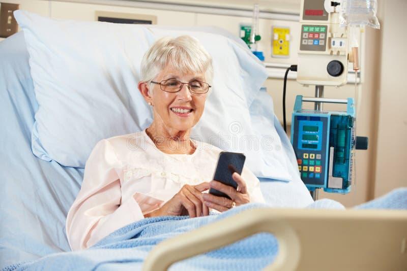 高级女性患者在使用移动电话的医院病床上 免版税图库摄影