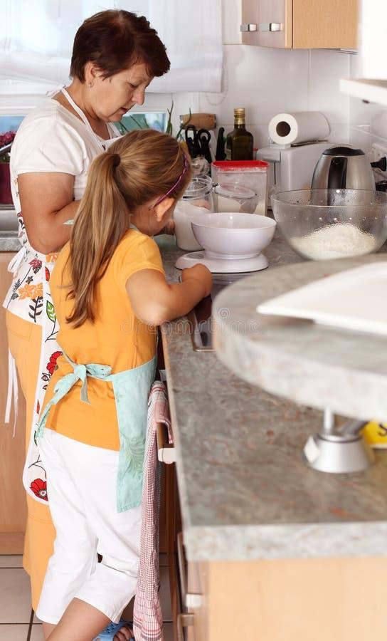 高级妇女和儿童烘烤 库存图片