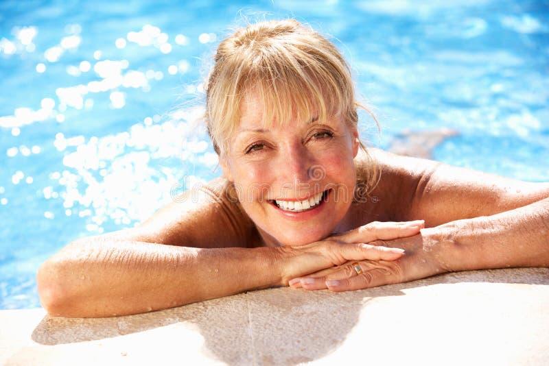 高级妇女获得乐趣在游泳池 免版税图库摄影