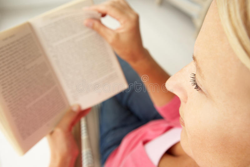 高级妇女阅读书在家 免版税库存照片