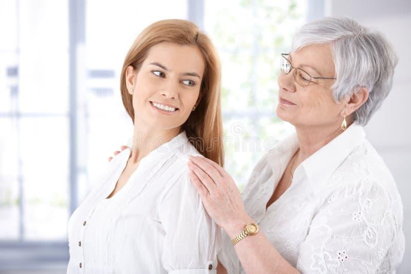 高级母亲和成人女儿微笑 免版税库存图片