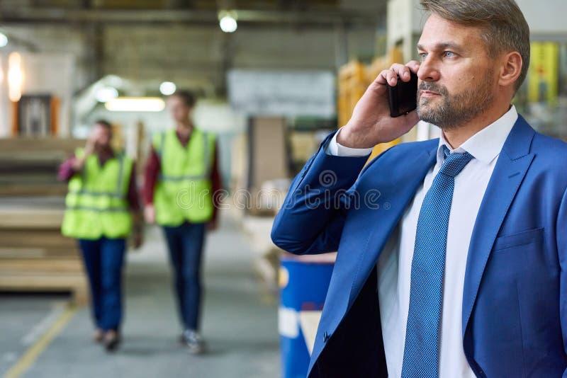高级管理人员讲话由电话在工厂 库存照片