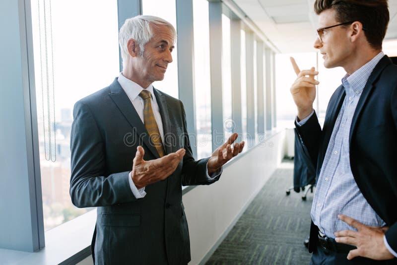 高级管理人员谈论与同事 库存图片