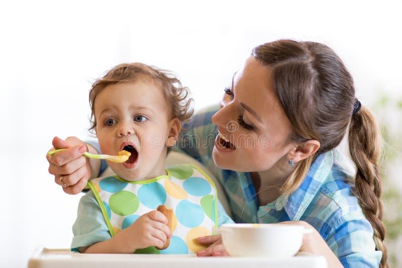 高脚椅子的妈妈哺养的婴孩 免版税库存照片