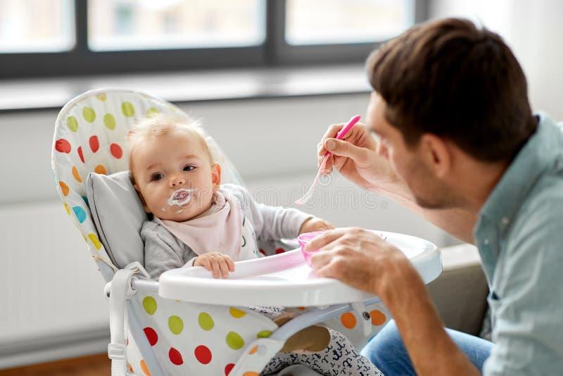 高脚椅子的父亲哺养的婴孩在家 图库摄影