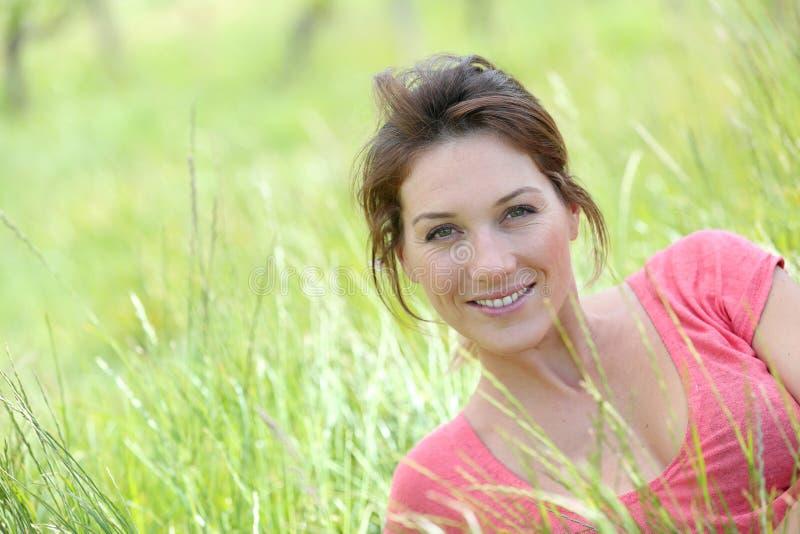 高草地的美丽的微笑的妇女 图库摄影