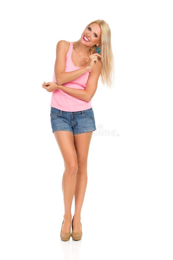 高跟鞋、短裤和桃红色无袖衫的笑的美丽的Blong妇女 库存图片