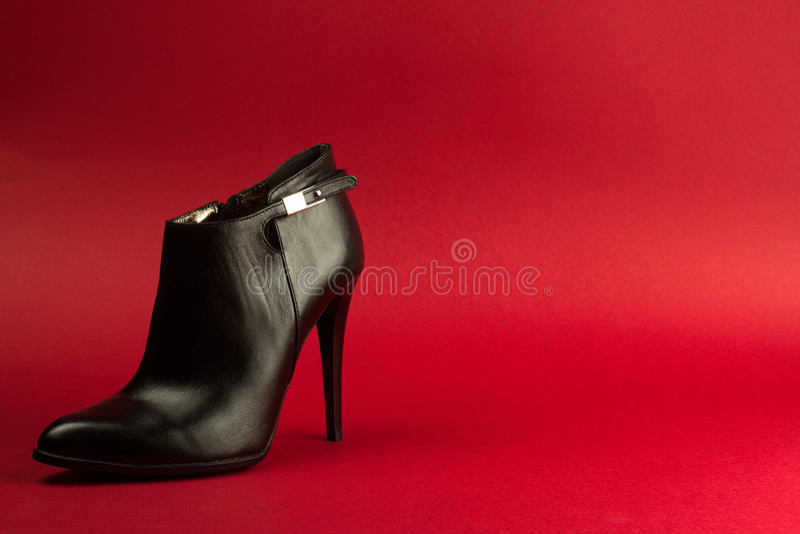 高跟鞋在红色背景的黑色鞋子 图库摄影