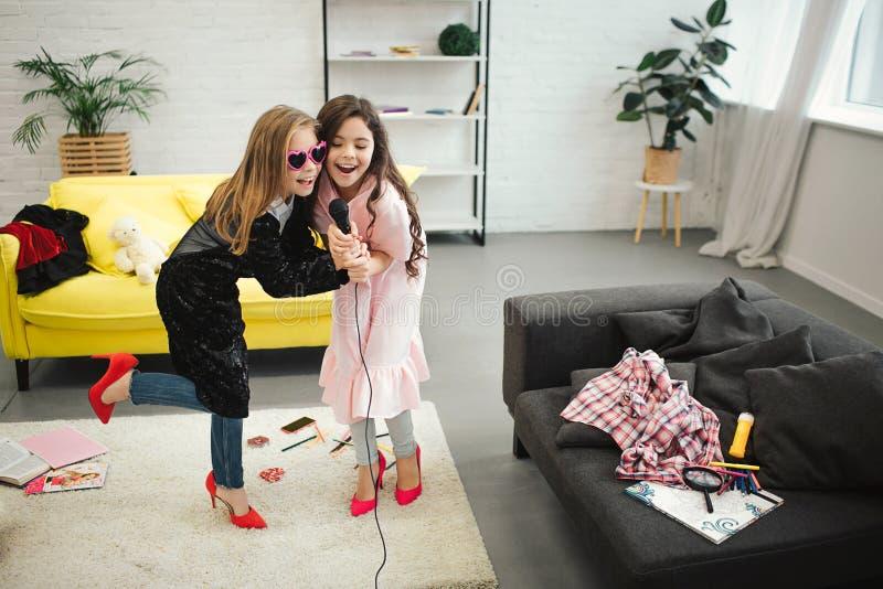 高跟鞋的十几岁的女孩相连话筒的和唱歌入它 他们穿衣裳和鞋子妇女的 免版税图库摄影