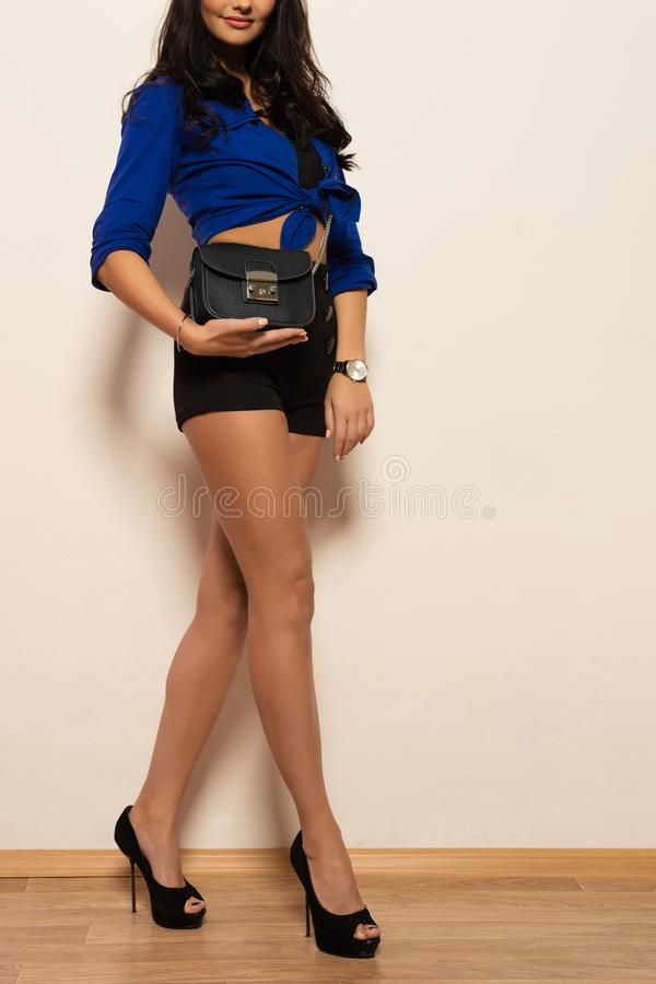 高跟鞋的美丽的时髦的年轻深色的妇女在手上拿着一台时兴的传动器 库存图片