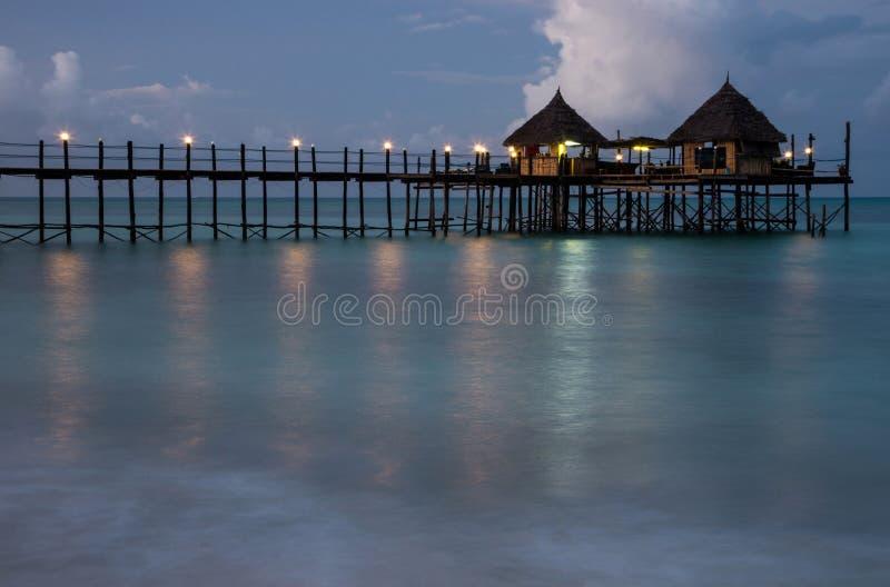 高跷的平房在水 日落的手段天堂在海洋 免版税图库摄影