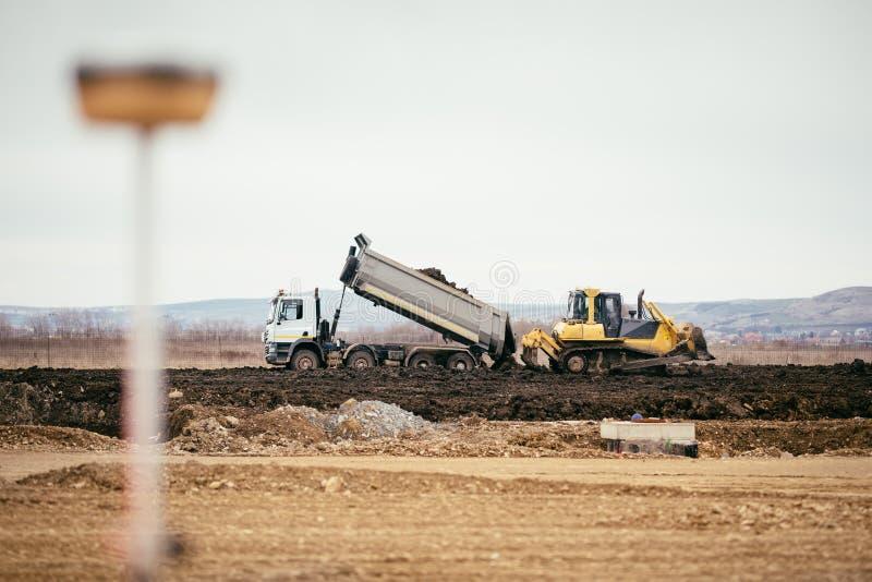 高速公路与倾销地球和推土机的倾销者卡车的建造场所发展成水平和推挤地球 库存照片