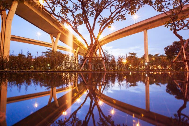 高速公路互换风景,在普密蓬桥梁的看法下在日落的,反射建筑学美好的形状  免版税库存照片