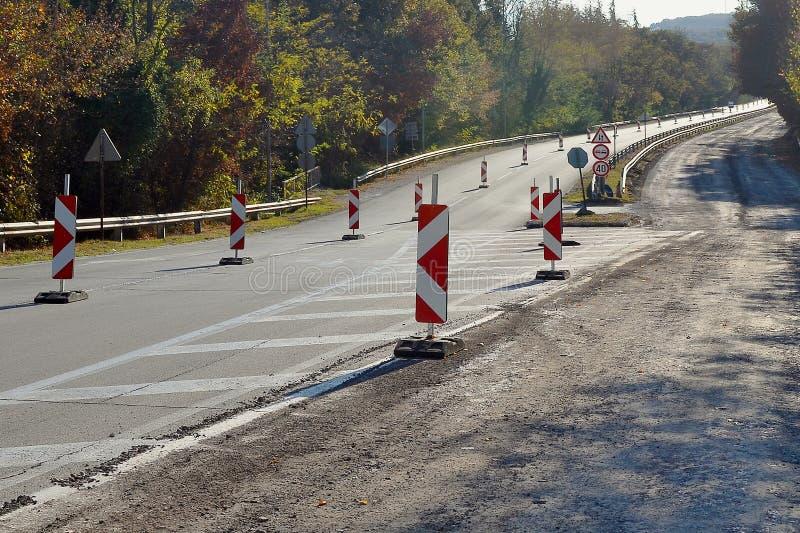 高速公路在修理期间的森林里在一秋天天:路的一半被阻拦,警报信号被安装 免版税库存图片