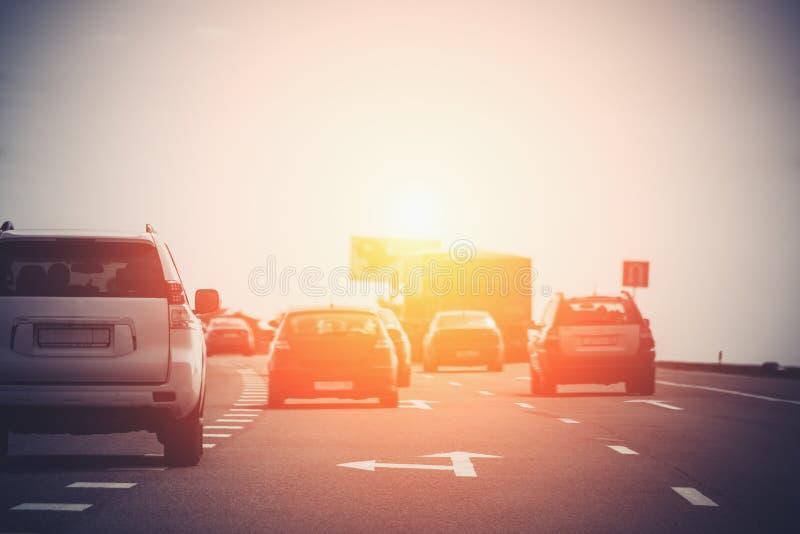 高速公路在日落光,在路的汽车的交通堵塞 免版税库存图片