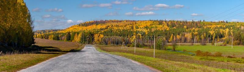 高速公路的全景通过秋天木头和领域在好日子,与在天空的云彩,从数的全景 库存照片