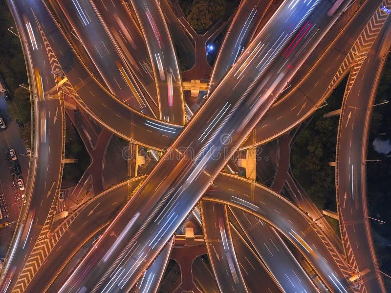 高速公路连接点鸟瞰图在与雾的晚上塑造信件x十字架 桥梁、路或者街道在运输概念 免版税库存照片