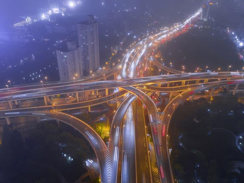 高速公路连接点鸟瞰图在与雾的晚上塑造信件x十字架 桥梁、路或者街道在运输概念 库存照片