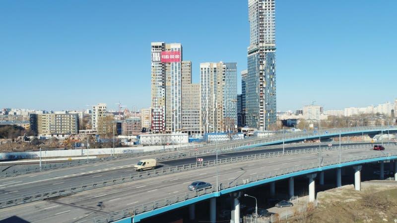 高速公路鸟瞰图有移动的汽车和高现代摩天大楼的背景的在反对蓝色的晴朗的夏日 图库摄影