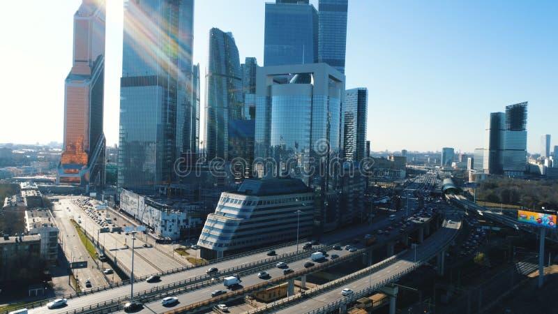 高速公路鸟瞰图有移动的汽车和高现代摩天大楼的背景的在反对蓝色的晴朗的夏日 免版税库存照片