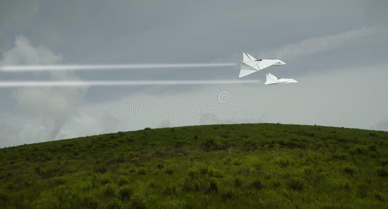 高速在绿草小山的白色喷气机 库存照片