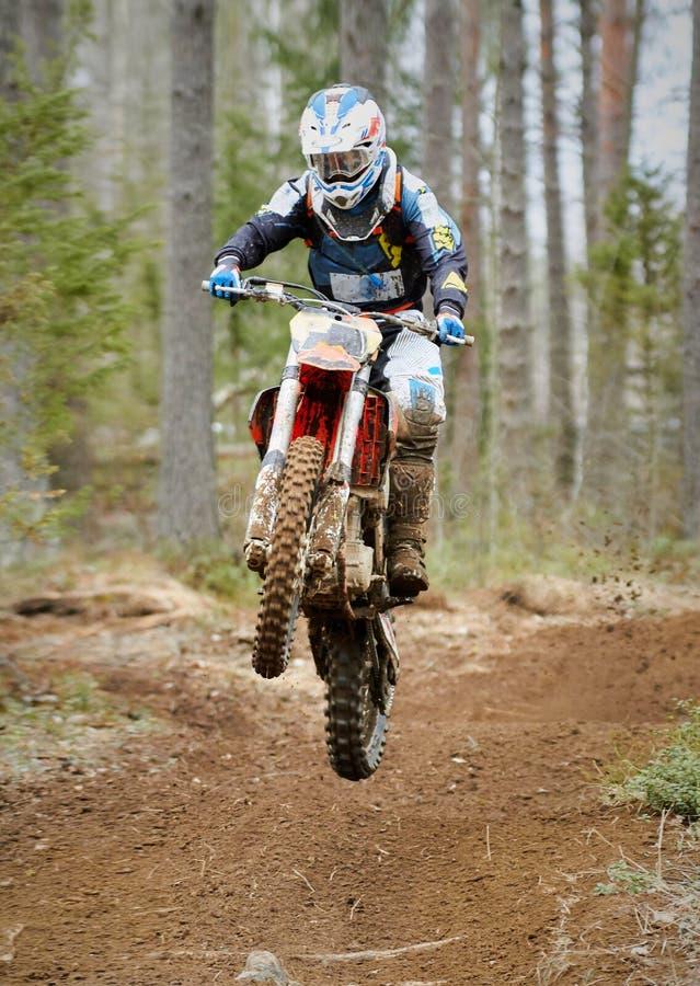 高速跳跃与自行车的摩托车越野赛司机在赛马跑道 免版税库存图片