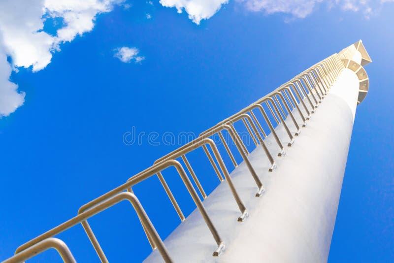 高金属建筑 — 一座白色灯塔塔,楼梯通往蓝天,从下到上都能看到 库存图片