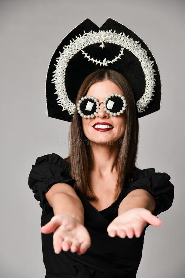 高雅和样式 华美的年轻女人演播室画象摆在反对灰色背景的一点黑礼服的 免版税库存照片