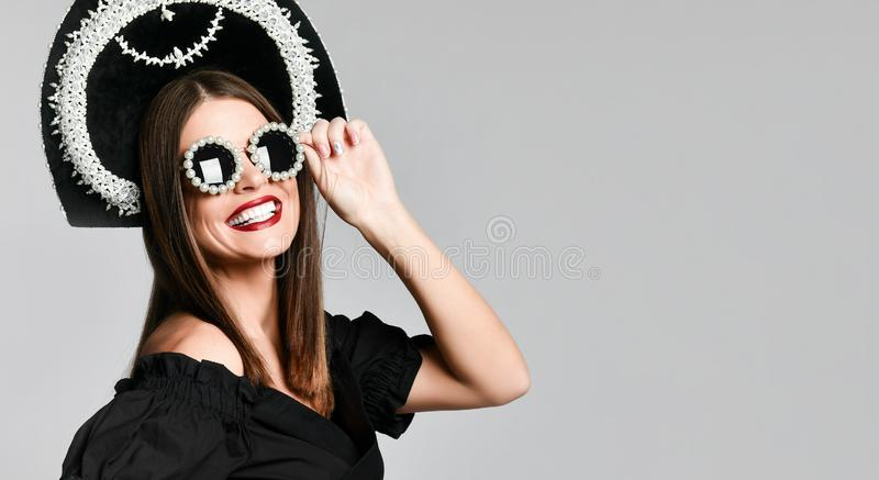 高雅和样式 华美的年轻女人演播室画象摆在反对黄色背景的一点黑礼服的 图库摄影