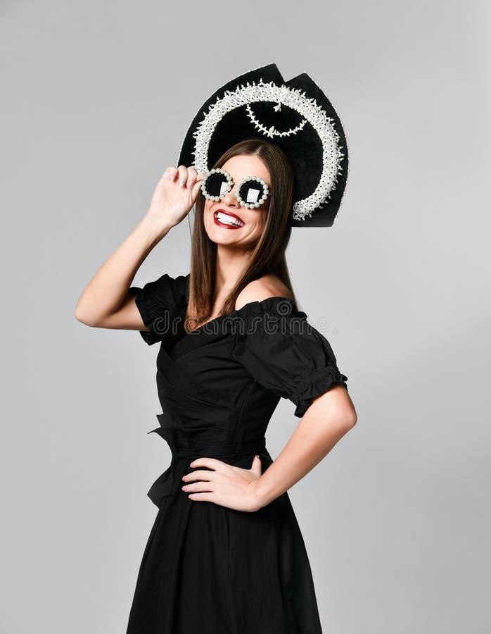 高雅和样式 华美的年轻女人演播室画象摆在反对黄色背景的一点黑礼服的 免版税图库摄影